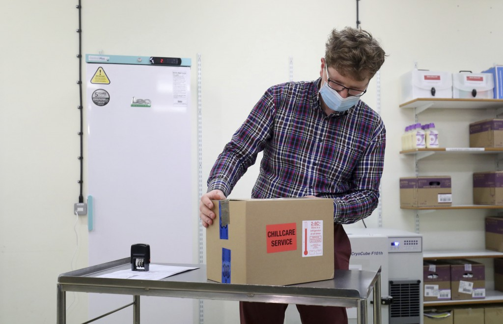 FILE - In this Saturday Jan. 2, 2021 file photo, Assistant Technical Officer Lukasz Najdrowski unpacks doses of the COVID-19 vaccine developed by Oxfo...