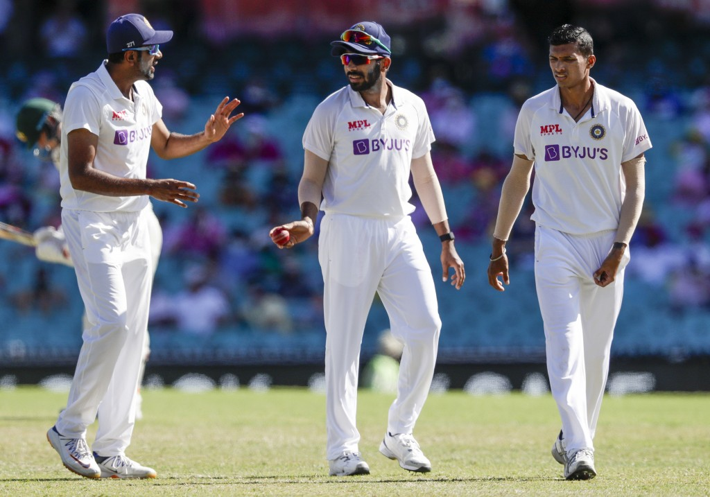 Indian bowlers Ravichandran Ashwin, left, Jasprit Bumrah and Navdeep Saini, right, talk during play on day three of the third cricket test between Ind...