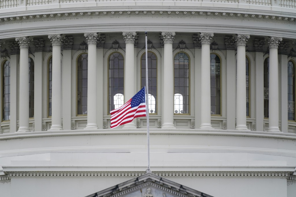 An American flag flies at half-staff in remembrance of U.S. Capitol Police Officer Brian Sicknick above the Capitol Building in Washington, Friday, Ja...