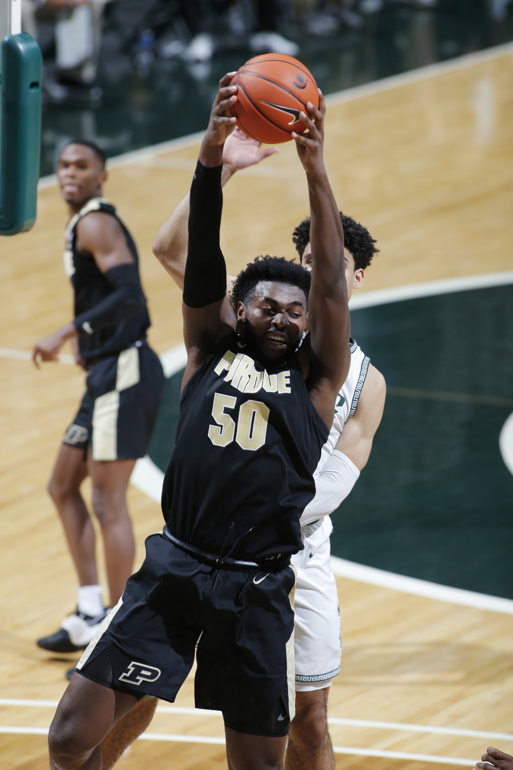 Purdue's Trevion Williams (50) pulls down a rebound in front of Michigan State's Malik Hall during the second half of an NCAA college basketball game,...