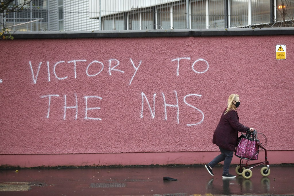 FILE - In this Tuesday, Dec. 8, 2020 file photo, a woman walks past graffiti with the words Victory to the NHS (National Health Service) on a wall at ...