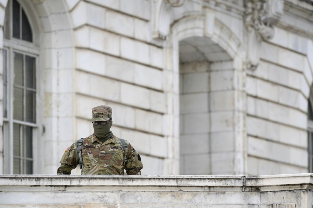 A member of the military stands guard outside Russell Senate Office Building on Capitol Hill in Washington, Friday, Jan. 8, 2021, in response to suppo...