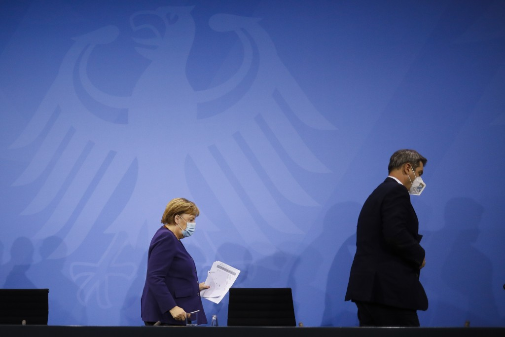 FILE - In this Wednesday, Dec. 2, 2020 file photo, German Chancellor Angela Merkel, left, and Bavarian govenor Markus Soeder, right, leave a news conf...