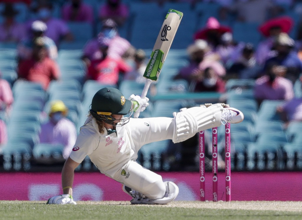 Australia's Will Pucovski falls while batting during play on day three of the third cricket test between India and Australia at the Sydney Cricket Gro...