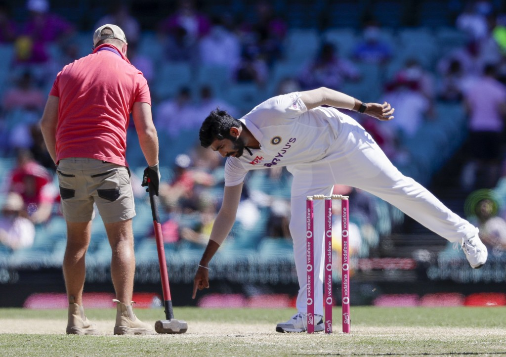 Indian bowler Jasprit Bumrah points to the pitch for a groundsman to work on during play on day three of the third cricket test between India and Aust...