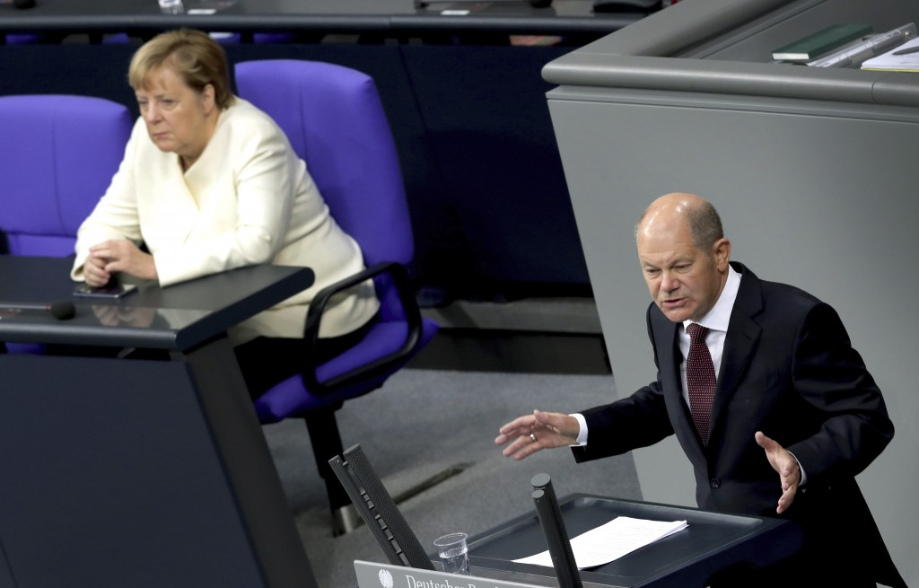 FILE - In this Sept. 29, 2020 file photo, German Finance Minister Olaf Scholz, right, delivers a speech beside German Chancellor Angela Merkel, left, ...
