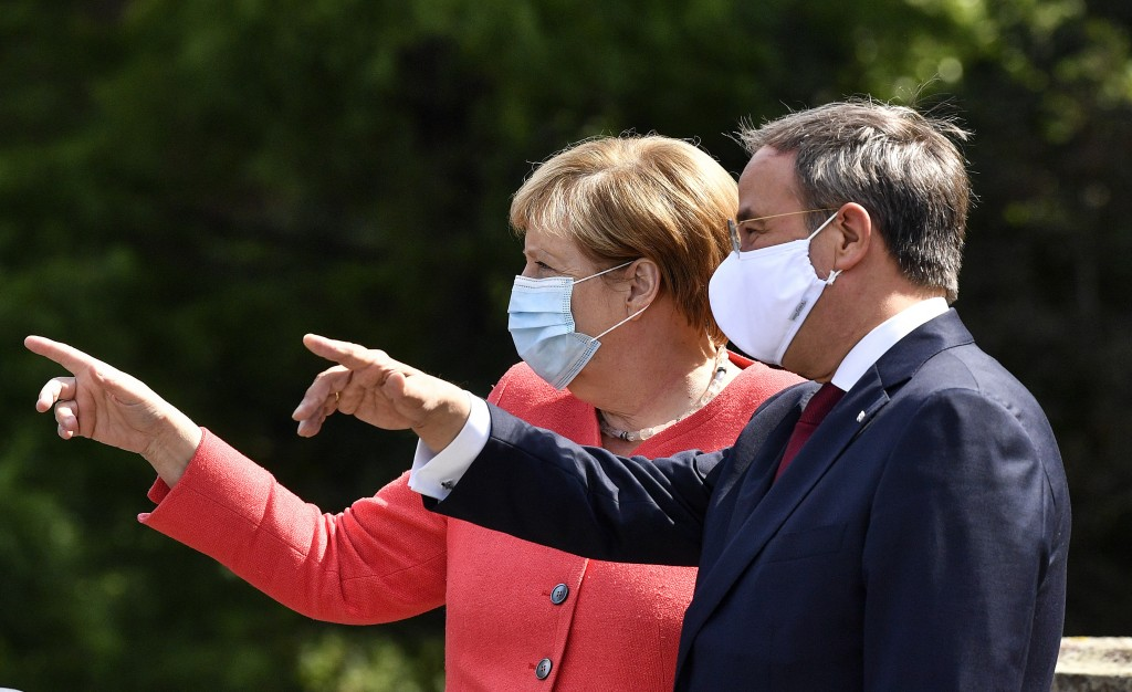 FILE - In this Aug. 18, 2020 file photo, German chancellor Angela Merkel, left, wears a face mask due to the coronavirus pandemic as she meets Governo...