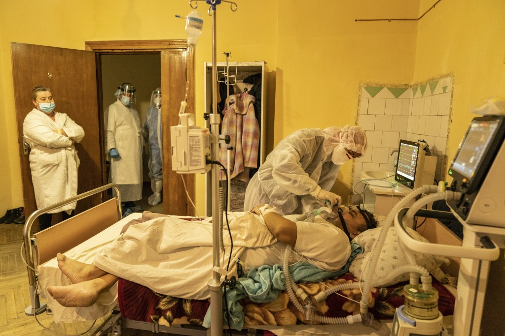 A medical worker treats Mykhailo Kaldarar, patient with COVID-19 as his wife Oleksandra Kaldarar, left, looks at him in a hospital in Rudky, Western U...