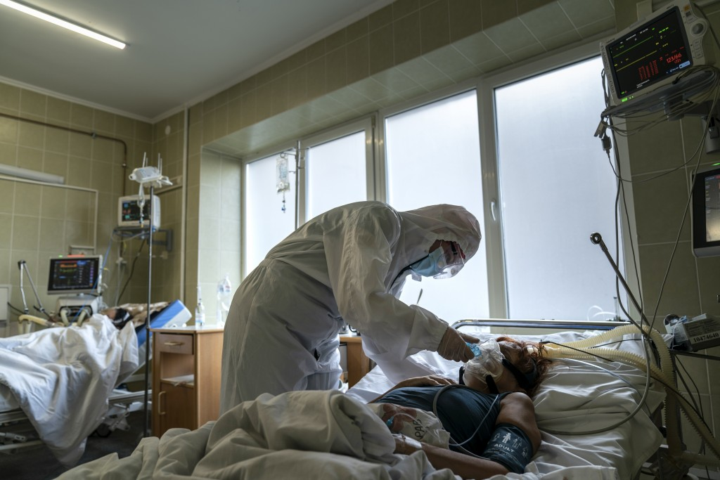 A nurse wearing a special suit to protect herself against coronavirus, treats a patient with COVID-19 in the ICU department of the emergency hospital ...