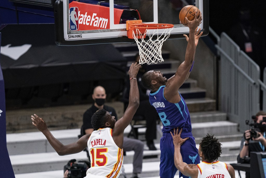 Charlotte Hornets center Bismack Biyombo (8) drives to the basket past Atlanta Hawks center Clint Capela (15) and forward De'Andre Hunter (12) during ...