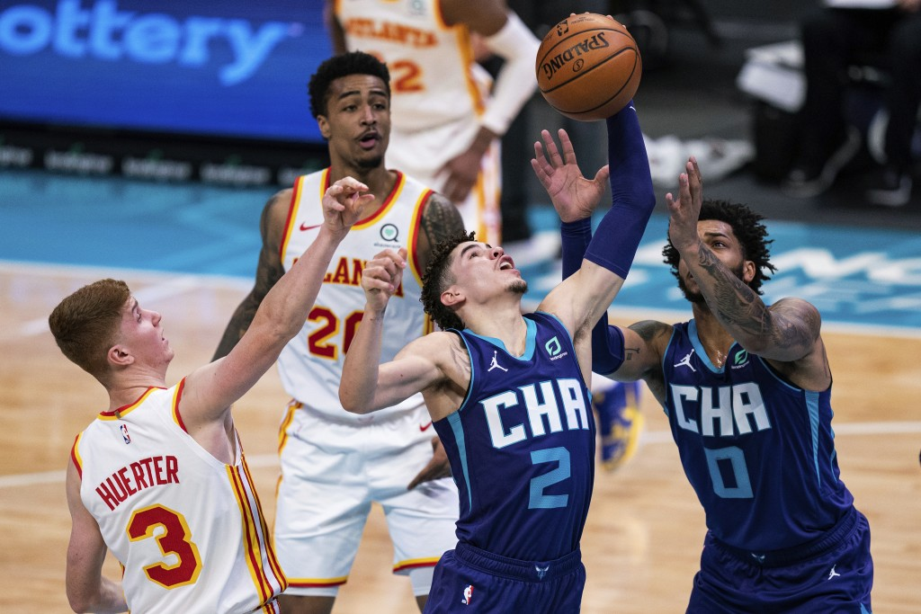 Charlotte Hornets guard LaMelo Ball (2) rebounds the ball next to Atlanta Hawks guard Kevin Huerter (3) during the first half of an NBA basketball gam...