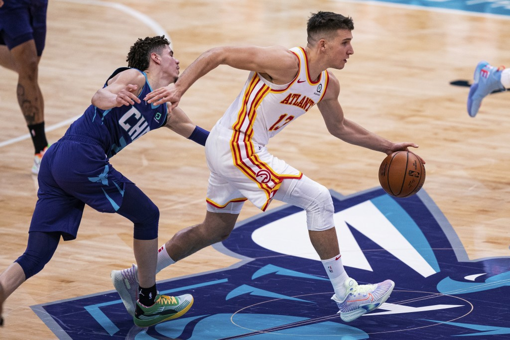 Atlanta Hawks guard Bogdan Bogdanovic (13) is fouled by Charlotte Hornets guard LaMelo Ball (2) during the first half of an NBA basketball game in Cha...