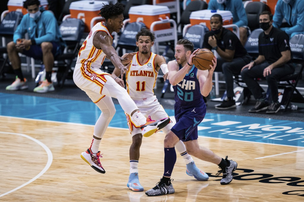 Charlotte Hornets forward Gordon Hayward (20) is defended by Atlanta Hawks forward De'Andre Hunter and guard Trae Young (11) during the first half of ...