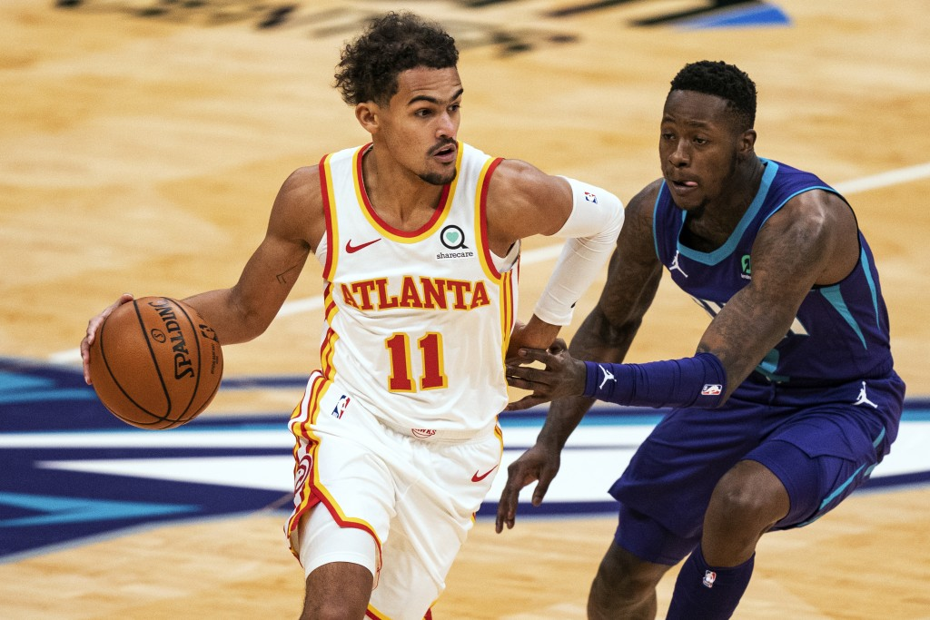 Atlanta Hawks guard Trae Young (11) dribbles around Charlotte Hornets guard Terry Rozier during the first half of an NBA basketball game in Charlotte,...