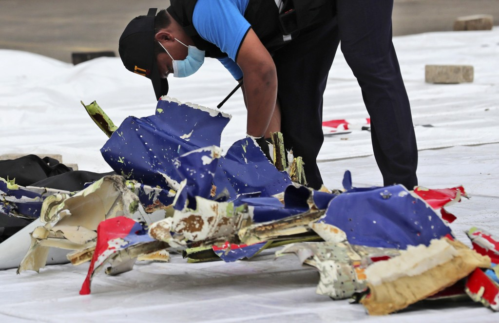 An investigator of Indonesian National Transportation Safety Committee inspects parts of Sriwijaya Air Flight 182 that crashed in the waters off Java ...