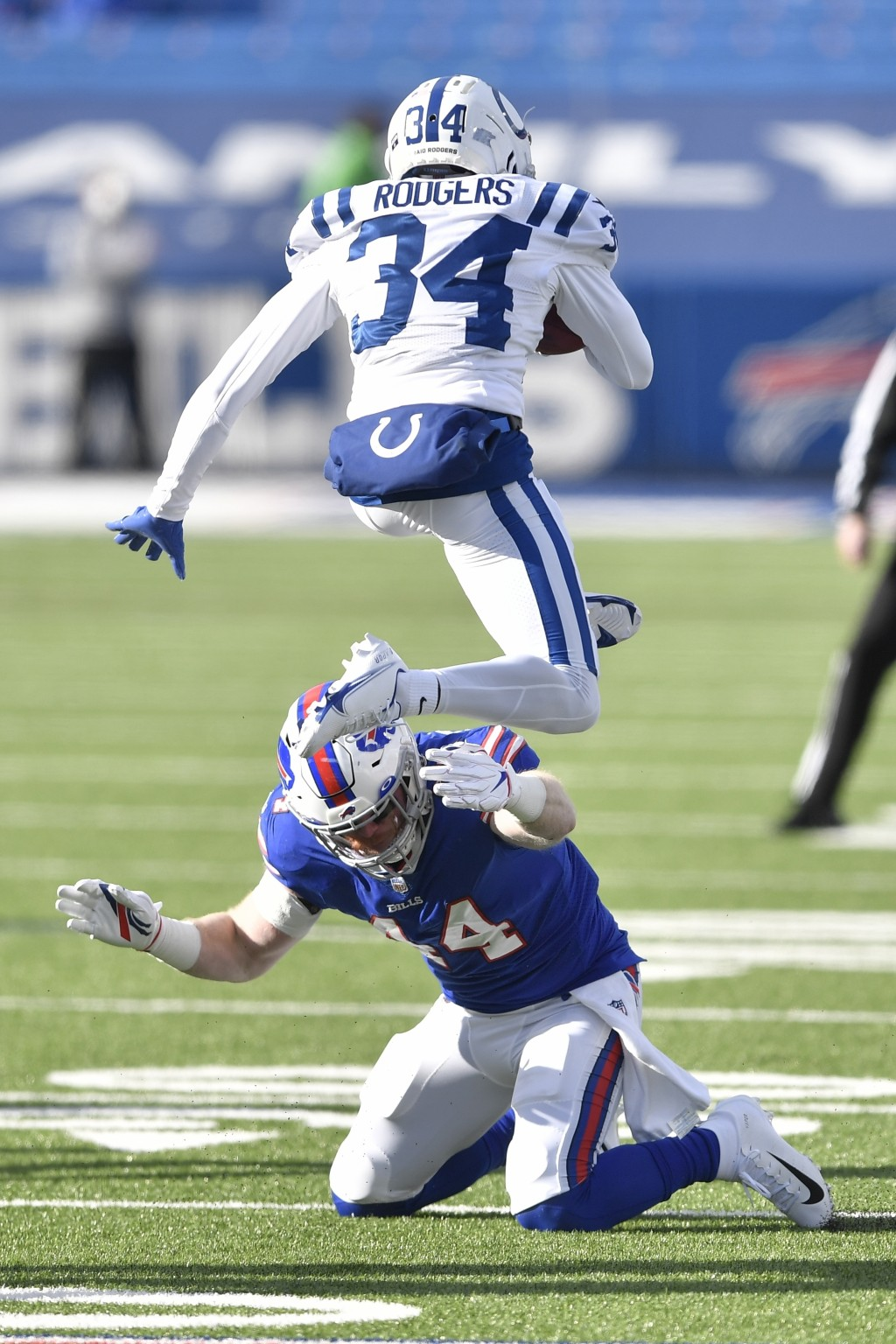 Indianapolis Colts' Isaiah Rodgers (34) leaps over Buffalo Bills' Tyler Matakevich (44) while while returning a kickoff during the first half of an NF...