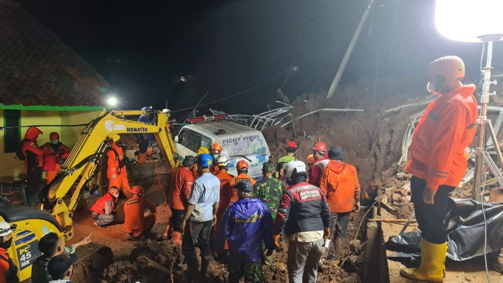 In this photo provided by the Indonesian National Disaster Mitigation Agency, rescuers work the scene of a landslide in Cihanjuang village, Indonesia,...
