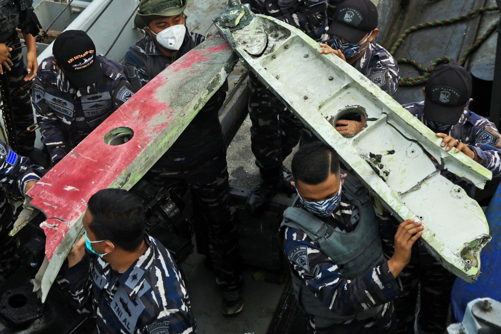 Indonesia navy sailors carry debris recovered from the waters off Java Island where a Sriwijaya Air passenger jet crashed on Saturday near Jakarta, In...