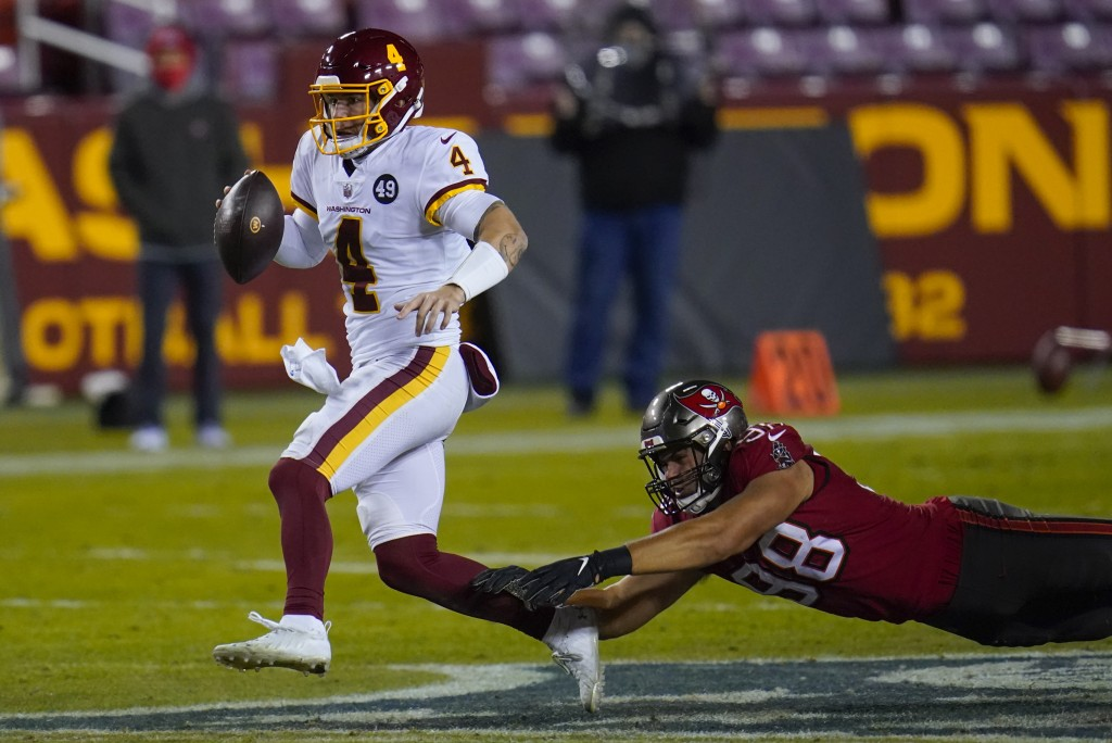 Washington Football Team quarterback Taylor Heinicke (4) his chased down by Tampa Bay Buccaneers outside linebacker Anthony Nelson (98) during the sec...