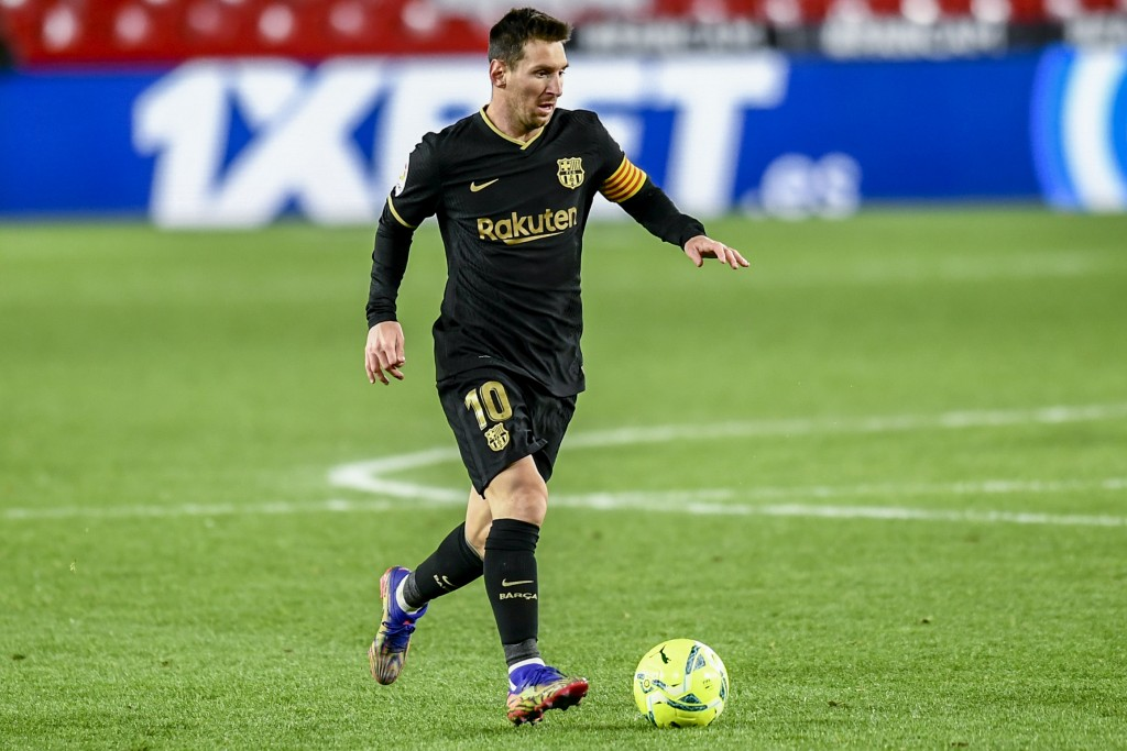 Barcelona's Lionel Messi runs with the ball during the Spanish La Liga soccer match between Granada and FC Barcelona at the Los Carmenes stadium in Gr...