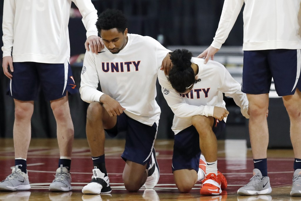 Virginia players kneel during the national anthem before an NCAA college basketball game against Boston College, Saturday, Jan. 9, 2021, in Boston. (A...