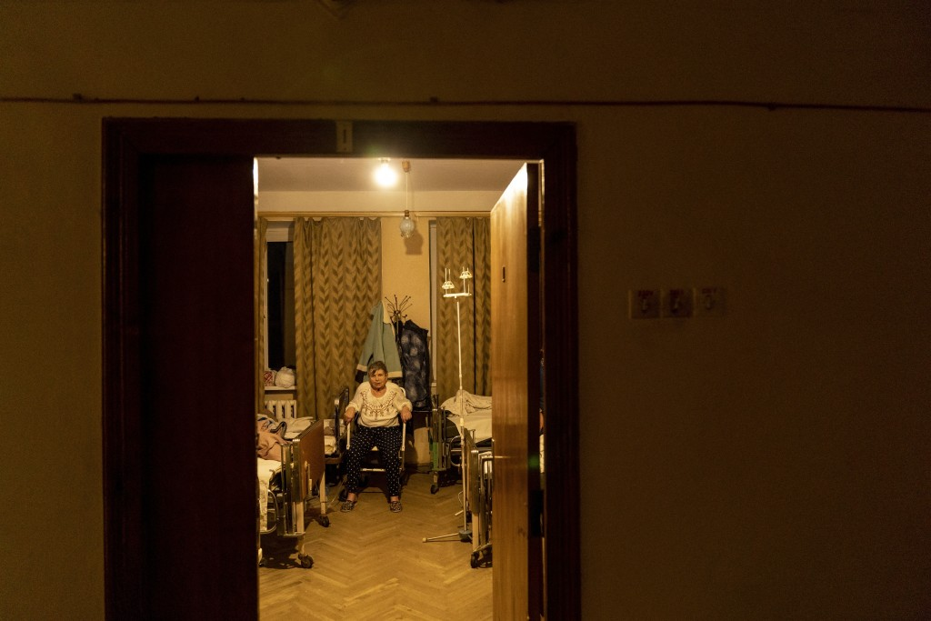 A patient with COVID-19 sits in a room at an hospital in Rudky, Western Ukraine, on Tuesday, Jan. 5, 2021. The government's wide-ranging lockdown clos...