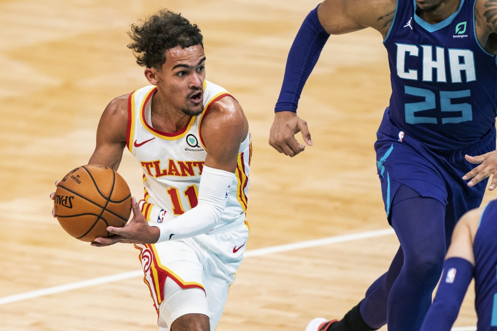 Atlanta Hawks guard Trae Young (11) drives to the basket past Charlotte Hornets forward P.J. Washington (25) during the first half of an NBA basketbal...