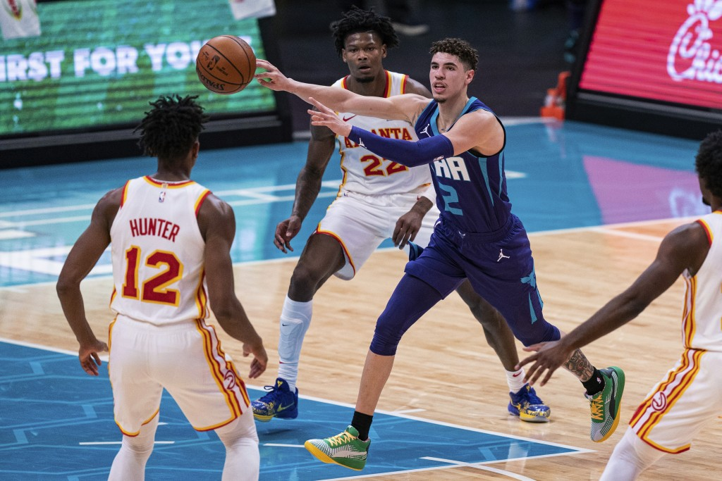Charlotte Hornets guard LaMelo Ball (2) looks away while passing the ball past Atlanta Hawks forward De'Andre Hunter (12) and forward Cam Reddish (22)...