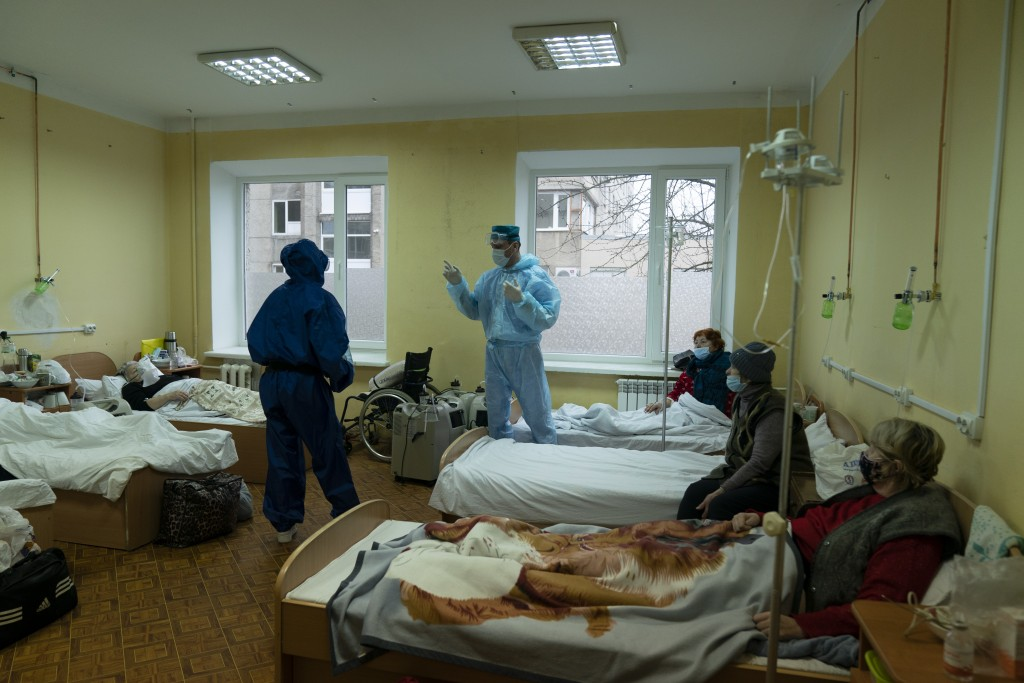 A medical worker talks with coronavirus patients in a hospital organized in the medical college in Lviv, Western Ukraine, on Monday, Jan. 4, 2021. A m...