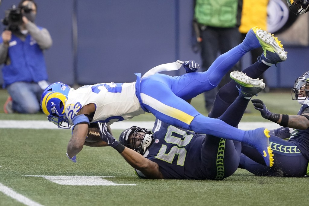 Los Angeles Rams running back Cam Akers (23) flips forward as Seattle Seahawks outside linebacker K.J. Wright (50) defends during the first half of an...