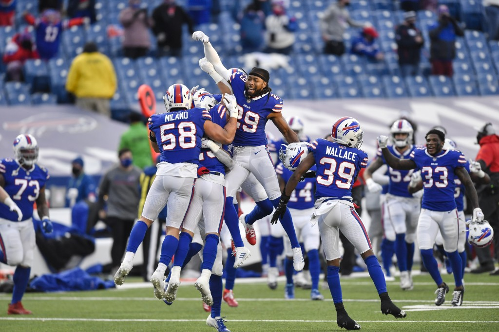 Buffalo Bills' Matt Milano (58) and Josh Norman (29) and teammates celebrate after an NFL wild-card playoff football game against the Indianapolis Col...