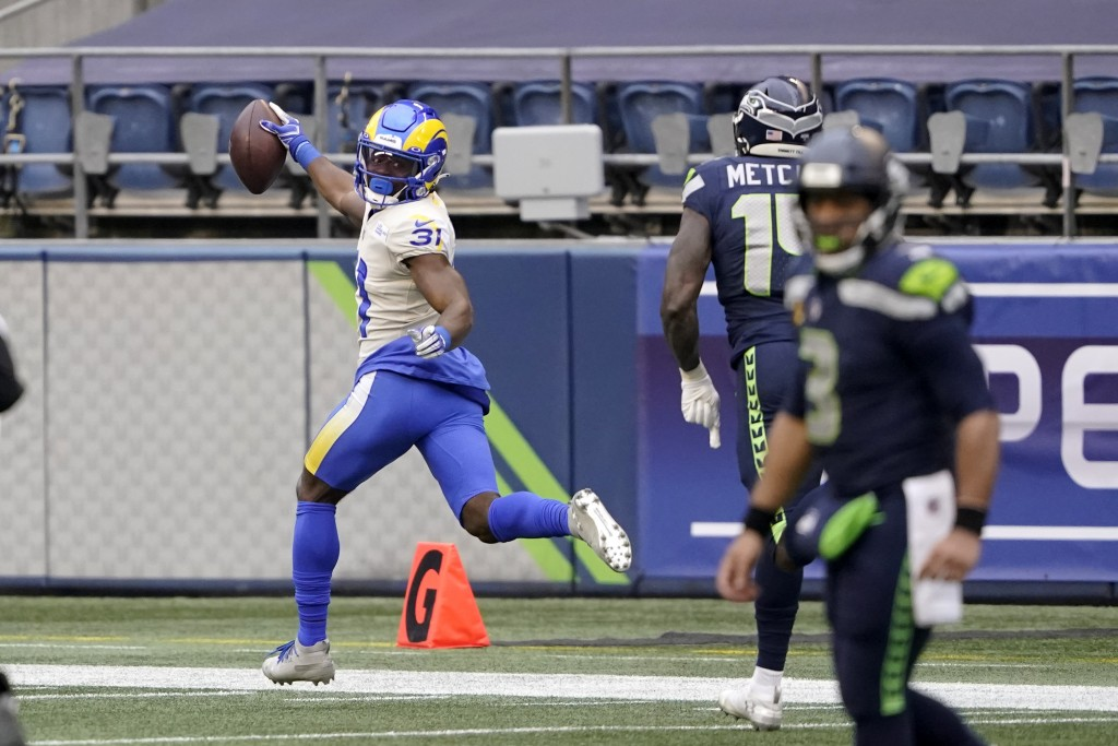 Los Angeles Rams defensive back Darious Williams (31) looks back as he scores on an interception from Seattle Seahawks quarterback Russell Wilson, rig...
