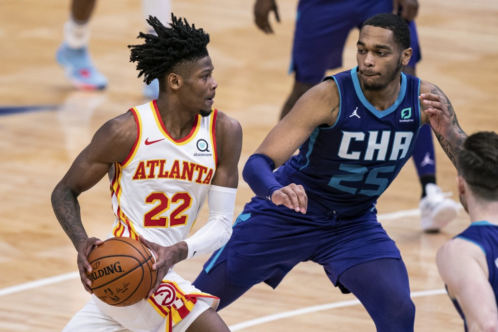 Atlanta Hawks forward Cam Reddish (22) drives to the basket while defended by Charlotte Hornets forward P.J. Washington (25) during the first half of ...
