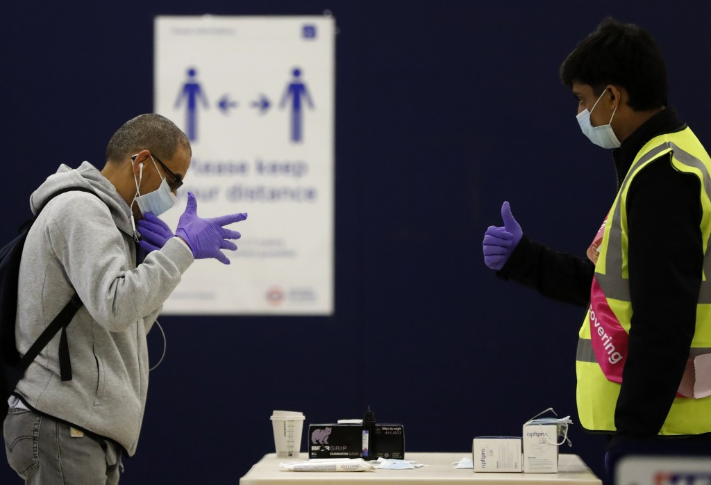 防疫如臨大敵。一名倫敦地鐵員工發送免費口罩、手套給有需要的乘客,並進行手部消毒。(美聯社圖片)