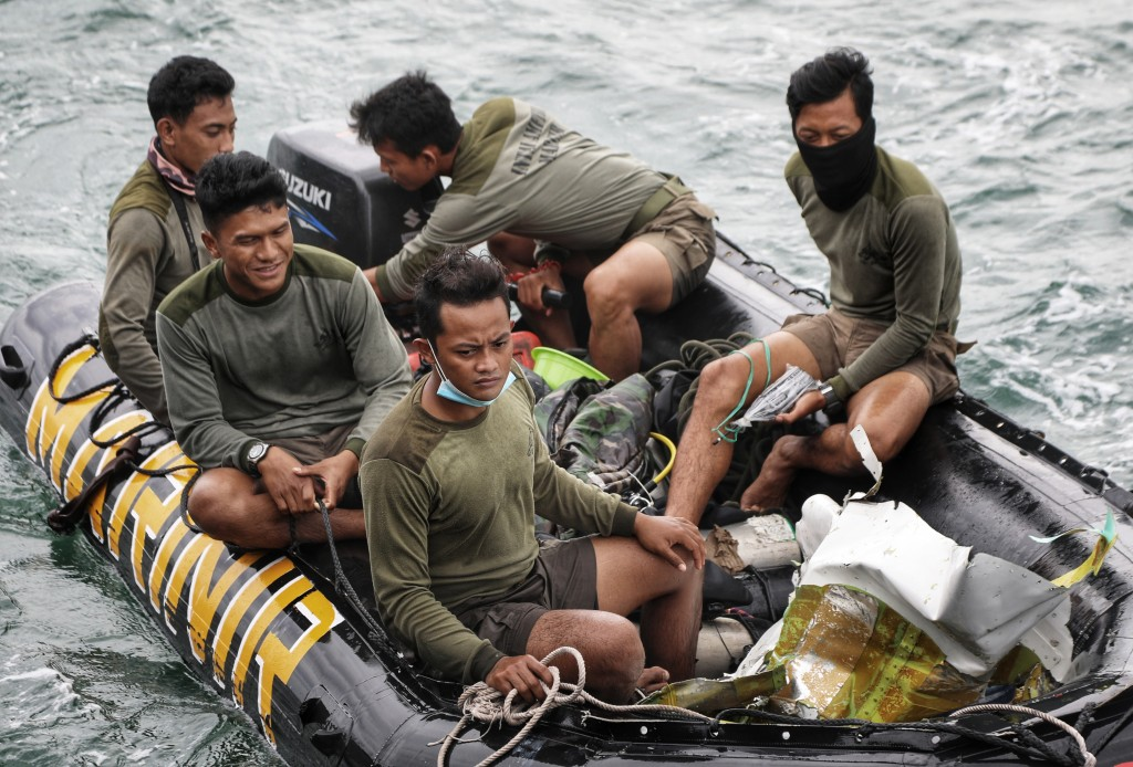 Indonesian Navy divers ride on a boat loaded with airplane parts recovered from the waters off Java Island where a Sriwijaya Air passenger jet crashed...