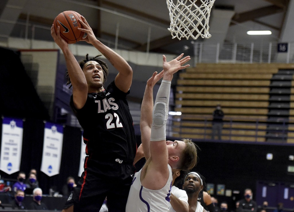 Gonzaga forward Anton Watson, left, drives to the basket as Portland forward Mikey Henn defends during the first half of an NCAA college basketball ga...