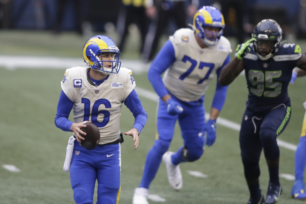 Los Angeles Rams quarterback Jared Goff (16) scrambles as he looks for room to pass against the Seattle Seahawks during the first half of an NFL wild-...