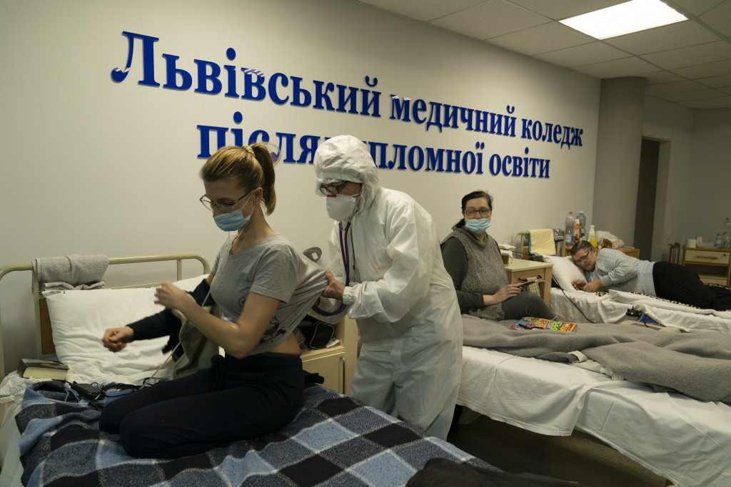 A medical worker checks on a coronavirus patient with a stethoscope in a hospital organized in the medical college in Lviv, Western Ukraine, on Monday...