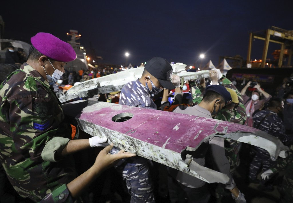 Soldiers and rescue personnel carry debris found in the waters off Java Island around where a Sriwijaya Air passenger jet crashed on Saturday, at Tanj...
