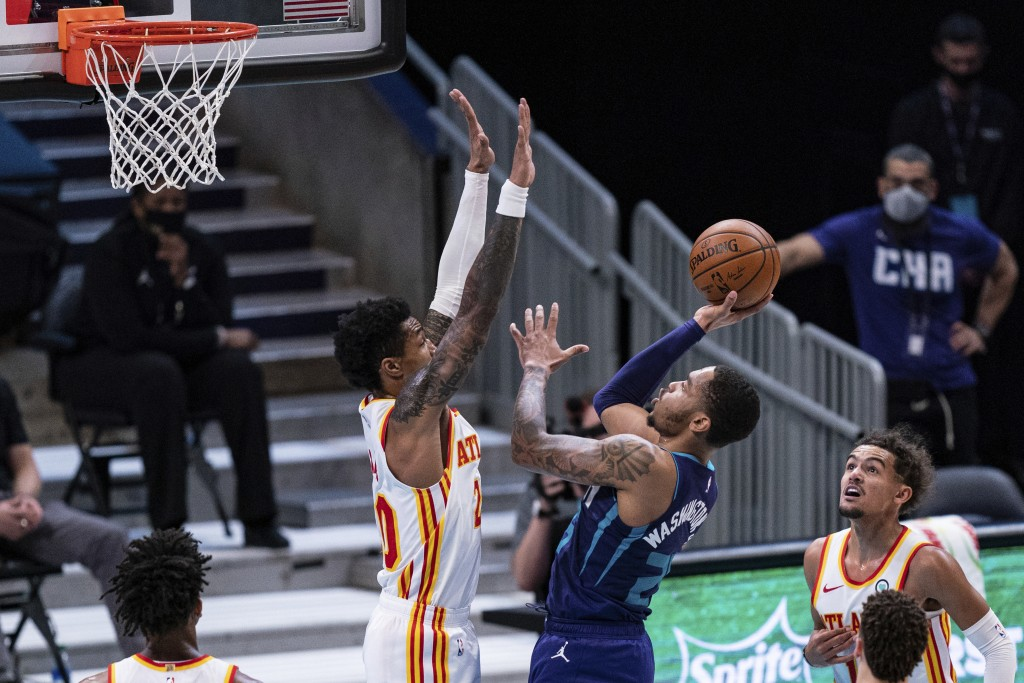 Charlotte Hornets forward P.J. Washington (25) tries to shoot over Atlanta Hawks forward John Collins (20) during the first half of an NBA basketball ...