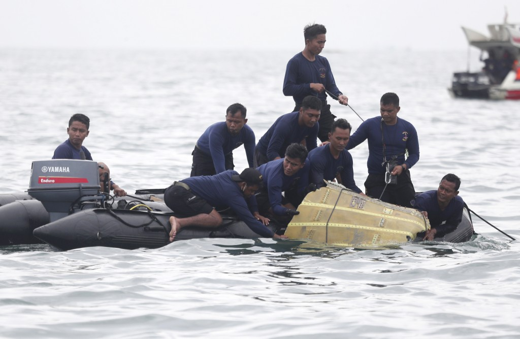 Indonesian Navy divers pull out a part of an airplane out of the water during a search operation for the Sriwijaya Air passenger jet that crashed into...