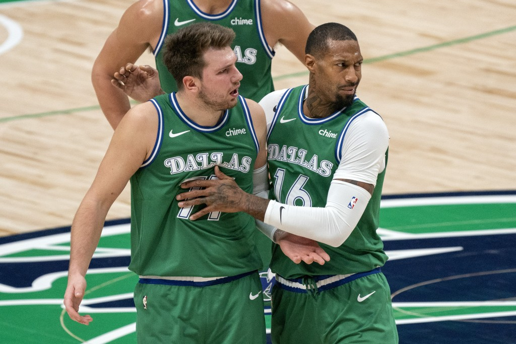 Dallas Mavericks guard Luka Doncic (77) is held back by forward James Johnson (16) as he argues with referees after being called for a technical foul ...