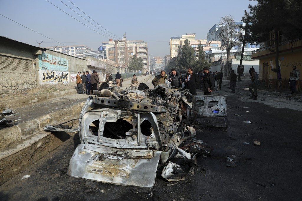 Afghan security officers inspect the site of a bomb attack in Kabul, Afghanistan, Sunday, Jan. 10, 2021. A roadside bomb exploded in Afghanistan's cap...
