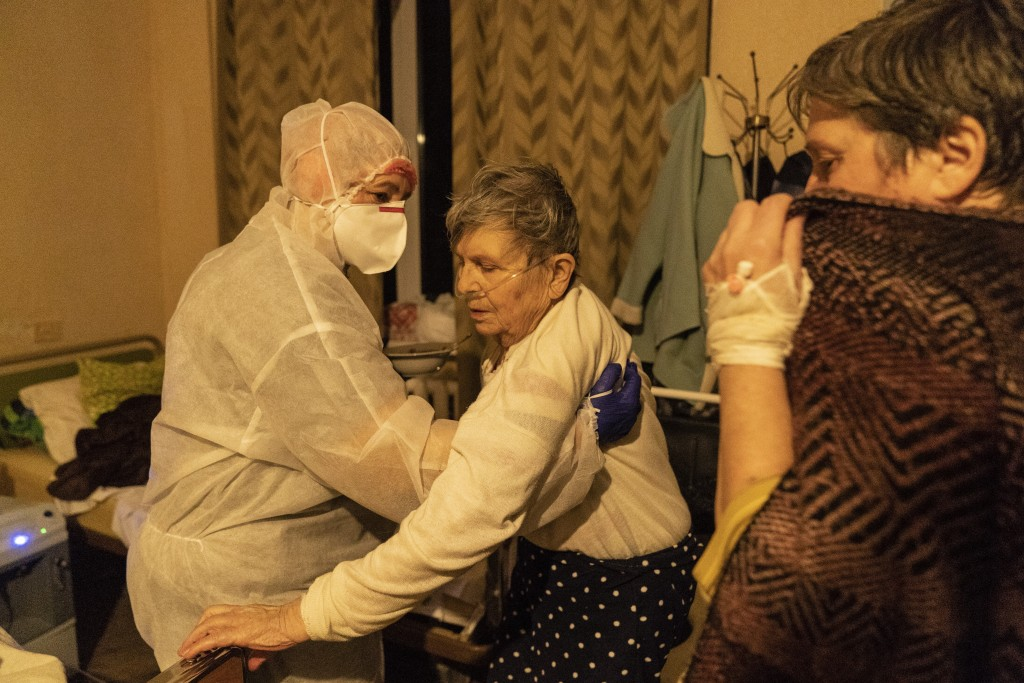 A medical worker helps a patient with COVID-19 to get up in a hospital in Rudky, Western Ukraine, on Tuesday, Jan. 5, 2021. Ukraine imposed a broad lo...