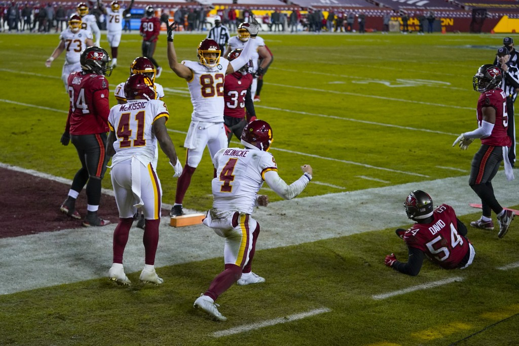 Washington Football Team quarterback Taylor Heinicke (4) celebrate his touchdown during the second half of the team's NFL wild-card playoff football g...