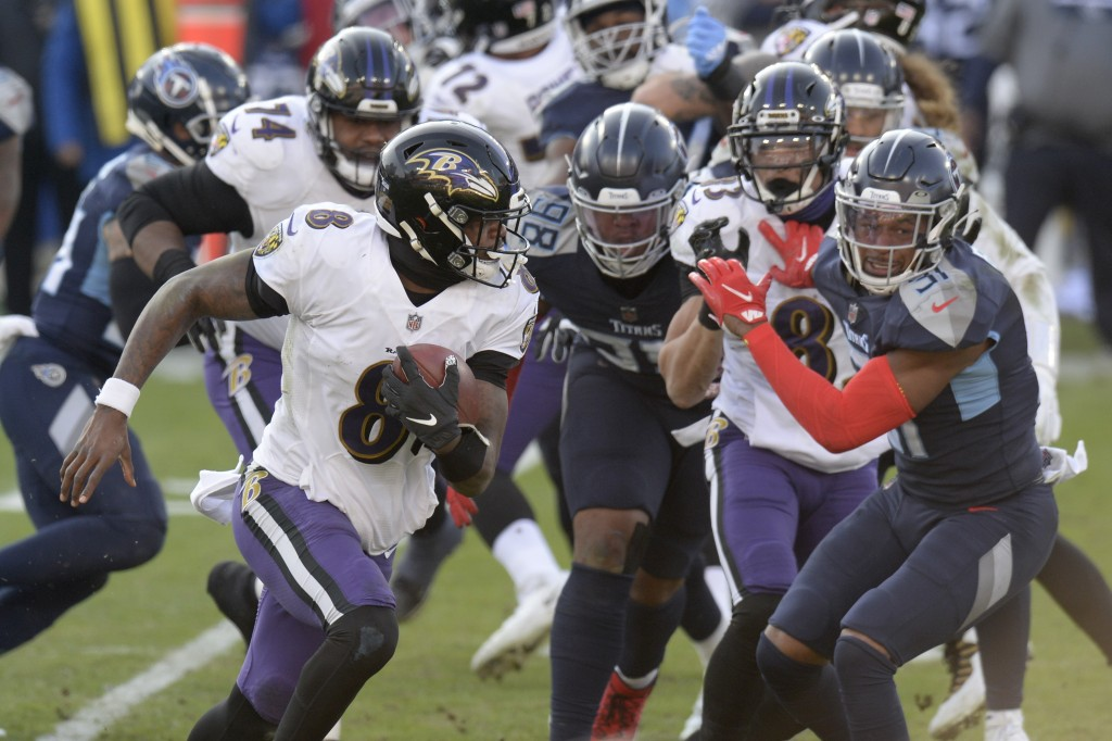 Baltimore Ravens quarterback Lamar Jackson (8) scrambles against the Tennessee Titans in the second half of an NFL wild-card playoff football game Sun...