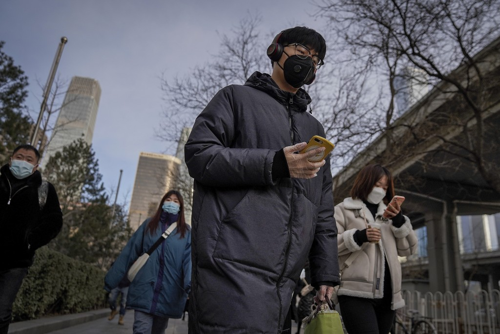 A man wearing a face mask and a disposable gloves to help curb the spread of the coronavirus heads to work with other masked people during the morning...