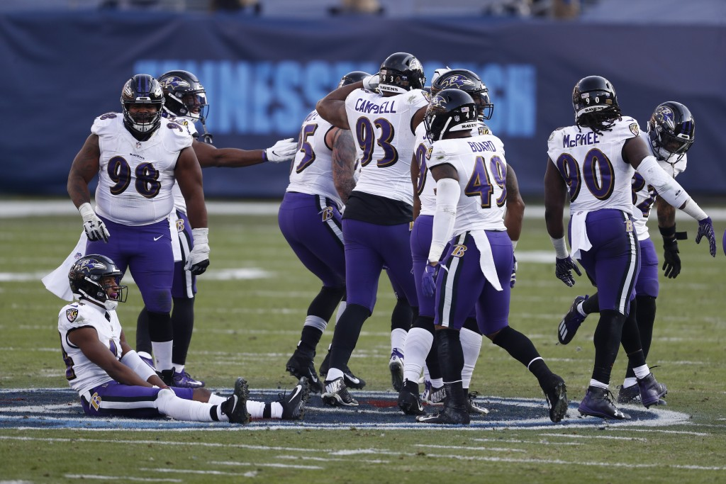 Baltimore Ravens players sit and stand on the Tennessee Titans' logo at the 50-yard line after Ravens cornerback Marcus Peters intercepted a pass agai...