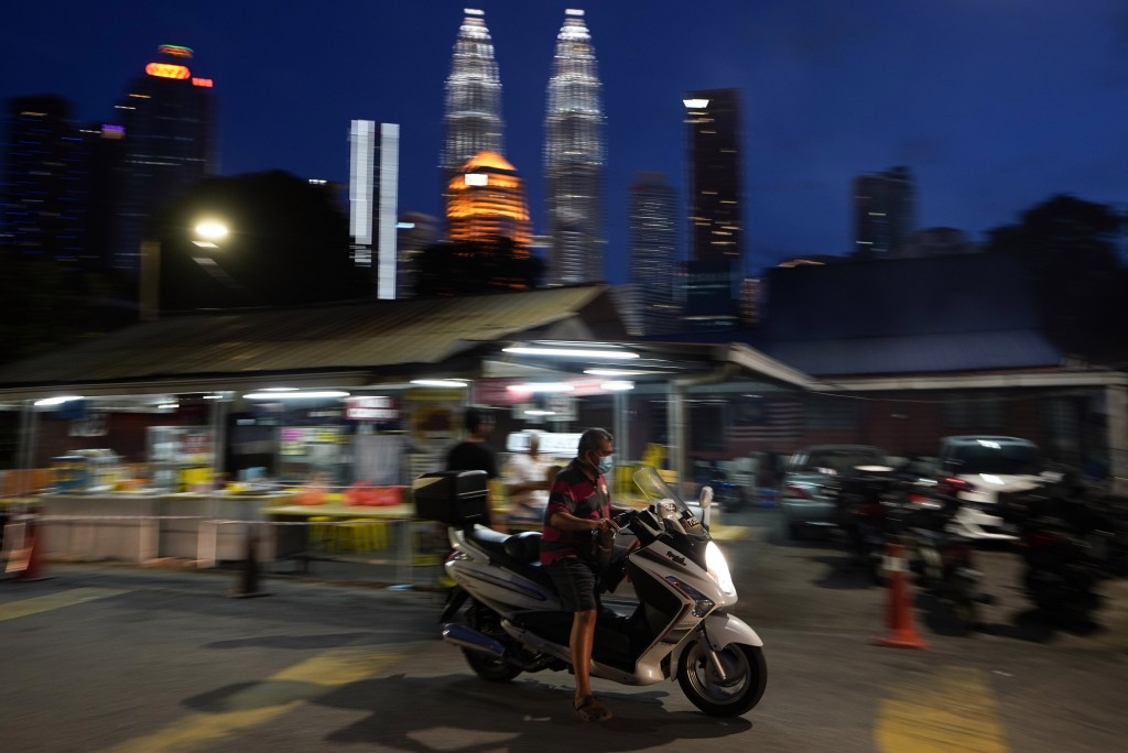 A motorcyclist wears a face mask with the background of Twin Towers in downtown Kuala Lumpur, Malaysia, Monday, Jan. 11, 2021. Prime Minister Muhyiddi...