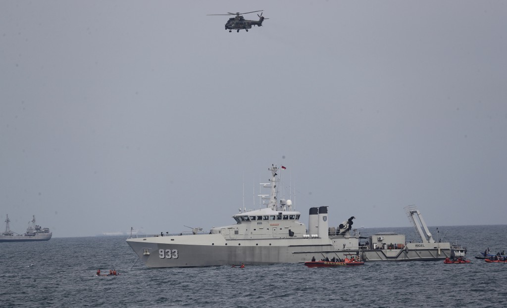 A military helicopter flies past as Indonesian Navy ships continue their search for the wreckage of Sriwijaya Air passenger jet that crashed into Java...